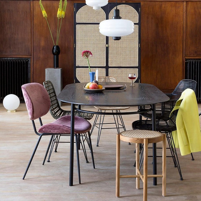 black oval dining table with natural cane webbing stool and velvet dining chairs
