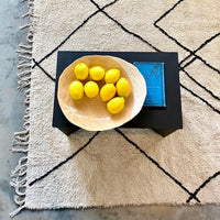 pastel colored decorative plate with lemons on a black side table