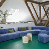 blue sofa and cream colored side tables on a green floor
