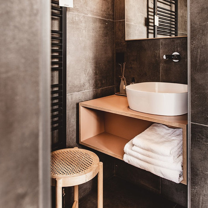 wooden stool with cane webbing in bathroom