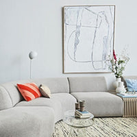 grey sofa with a red and pink swirl pillow and a ream stitched lines pillow and a large white abstract painting