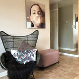 living room with rattan egg chair, black sheepskin and art work photo on wall