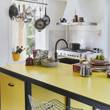 yellow colored countertop with ceramics from bold&basic collection including a silver colored, stoneware tea pot