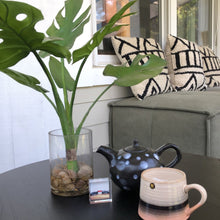 artificial monstera in glass vase on table on patio with teapot and mug
