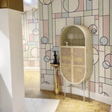 geomatric shaped wall paper with retro style oval shaped cane webbing cabinet in light grey