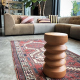 small terracotta side table in a living room with large sofa