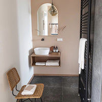 bathroom with sand colored walls, natural rattan chair and an arch shaped mirror with brass frame on wall above vanity