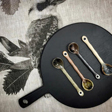 black cutting board with set of ceramic tea spoons