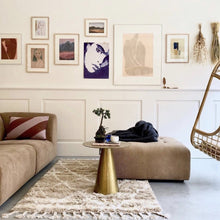 gallery wall with art and brown sofa
