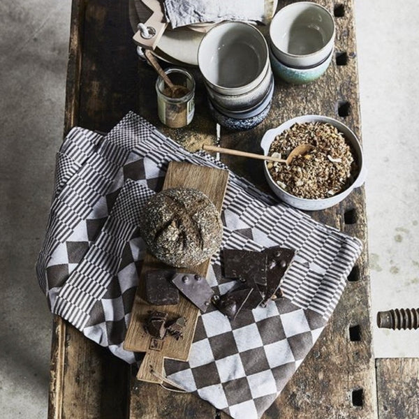 rustic style breakfast table scape with granola, bread, teak wooden servingboards and a brown checkered traditional Dutch cotton tablecloth