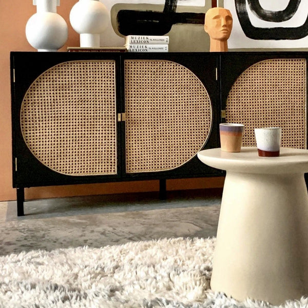 earthenware side table with a black sideboard with cane webbing doors