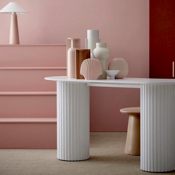 pink stairs and walls with an oval shaped white console table with pillar legs and blush colored flower vases