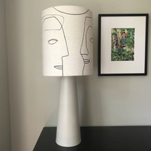 printed lamp shade with faces on a grey base