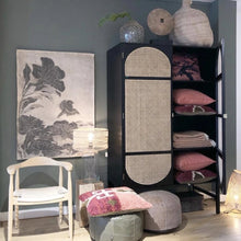 retro black cabinet with cane detail doors filled with pillows