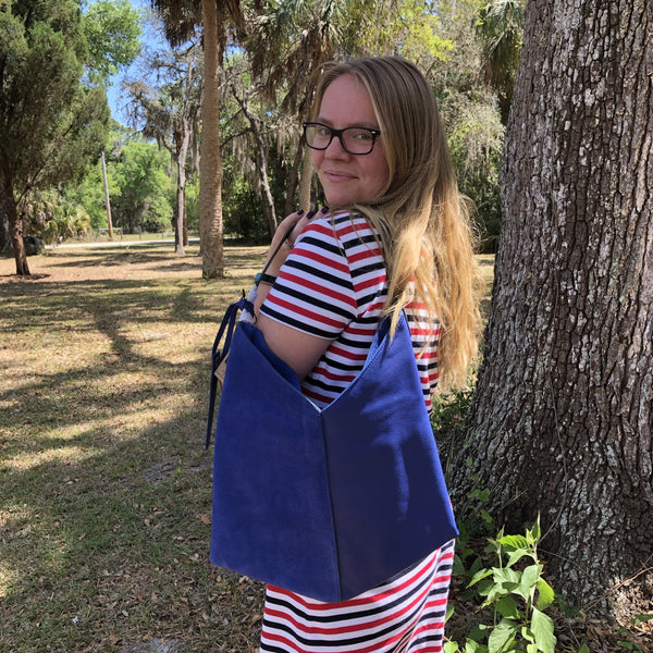 amber in striped dress and blue leather bag