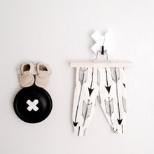 wall hook in black with baby shoes on top