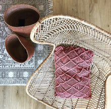 macreme textured throw pillow in terra red in natural rattan egg chair