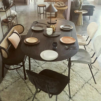 black oval dining table with grey and cream chairs and black wooden bench