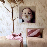 wallpaper with vintage reed design, brown sofa with striped pillow and art work with girl blowing a big bubble