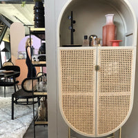 details of oval shaped retro style cabinet with cane webbing doors