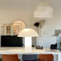 medium size wicker basket light in white above a kitchen island with a white acrylic mushroom table lamp and brass counter stools