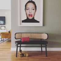 black retro cane webbing bench with angelina jolie photo and pink chanel bag