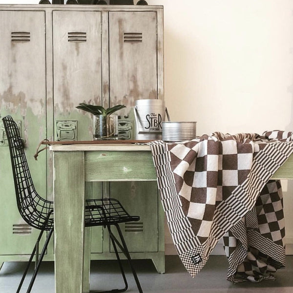 modern, rustic interior with a green table, black chair and brown and white traditional Dutch cotton tablecloth