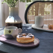 oval plate and coffee cup in pastel colors with donuts on a black table