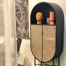black oval cabinet with terracotta head sculpture and coral vase