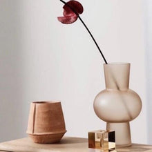 stillife with terracotta flower pot and peach colored glass vase