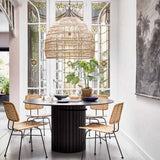 black pillar dining table with large wicker pendant and 4 natural rattan dining chairs