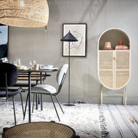 oval shaped cabinet with cane webbing doors in a dining area with a grey wall