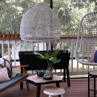 covered porch with black furniture and white wicker basket light