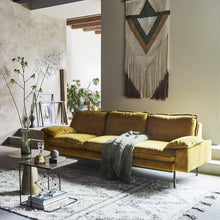 living room with ochre velvet sofa, nesting table and coffee table