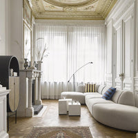 inerior with high ceiling that has a mural, a grey sofa and an oval shaped cabinet in black with cane webbing doors