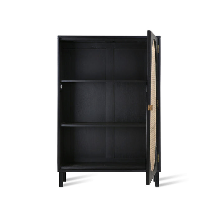 inside of a black, single door cabinet with cane webbing accent