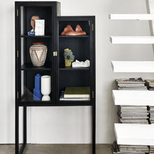 glass and black wood showcase cabinet in staircase shape next to a white staircase