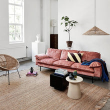 living room with pink sofa and natural color earthenware side table