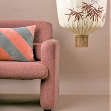 tangarine and grey striped pillow on a coral pink sofa and a painted lantern