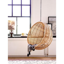 rattan hanging bowl chair and table lamp with jungle print in window.