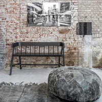 loft with exposed brick wall and black garden bench in wood by hk living and black leather pouf