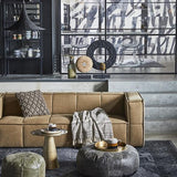 khaki brown couch and leather poufs with brown throw blanket in living room