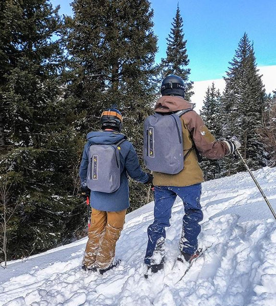 A couple enjoying a day walking in the snow with their Quietkat DayPack on.