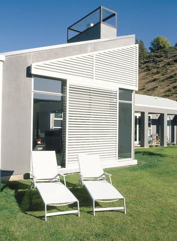 modern home with white sun shutters and two recliner outdoor chairs