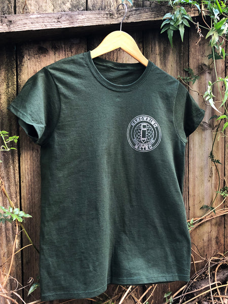 "A forest green shirt with a metallic silver print on the upper left side of the chest. The print is a circular shape, in the style of a subway token, with an image of a cut-out pencil in the center. There is outlined text arched above the image that says ""NANOWRIMO,"" and below that says ""METRO."" Immediately below the image is solid text that says ""GOOD FOR ONE NOVEL."""