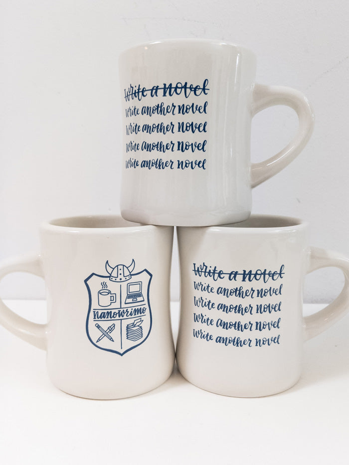 "The 2019 NaNoWriMo diner mug is cream colored with a navy print. If you're holding the mug in your right hand, the side facing you features the text ""Write a novel"" crossed out, followed by ""Write another novel"" listed four times and not crossed out. On the other side, there is a hand-drawn version of the classic NaNoWriMo logo."