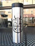 The travel cup has the NaNoWriMo shield on one side, with the Viking helmet on top and four squares inside the shield containing a steaming coffee cup, a computer, crossed pens, and a stack of paper with the top pieces curling up.