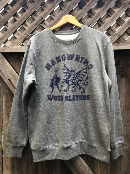 A heather grey crewneck sweatshirt with the words NaNoWriMo Word Slayer around the outside in a purple collegiate-style typeface. In the center of the shirt is an illustration of a knight holding a sword with a crown hovering over their head, facing an illustration of a dragon standing with wings outspread.