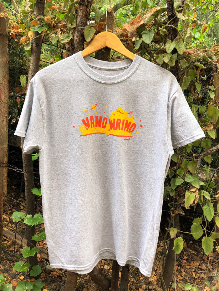 "A heather gray T-shirt features an open book with a red cover and yellow pages. The words ""NaNo"" and ""WriMo"" pop out of the book in red, with ""2020"" in red under the book. Red rose buds, a yellow and red deer, a yellow cloud, a small planet, and paint splatter all burst out from the book."