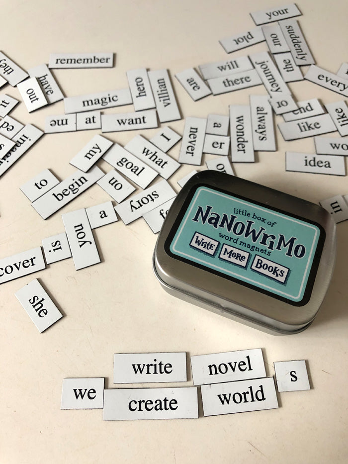 "A small metal tin with a sticker on the top that says ""little box of NaNoWriMo word magnets"" and illustrated magnets that say ""Write"", ""More"", and ""Books"" beneath. The sticker is a light blue and the text is dark blue."
